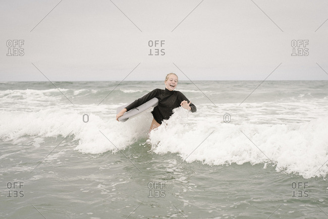 Blond girl bodyboarding in the ocean.