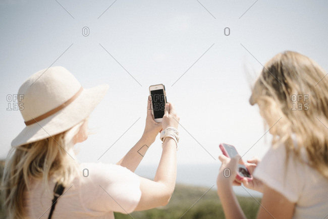 Woman and teenage girl with long blond hair standing outdoors, holding up a mobile phone, taking a picture.
