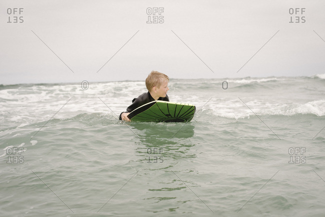 Blond boy bodyboarding in the ocean.