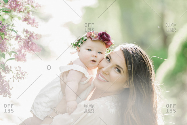 Portrait of a smiling mother and baby girl with a flower wreath on her head.