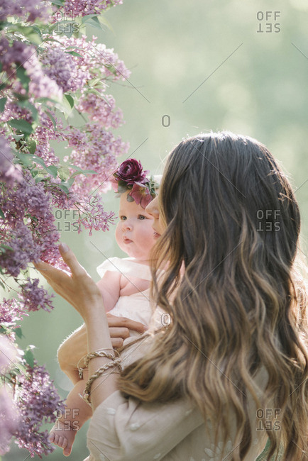 Mother holding baby girl with a flower wreath on her head.