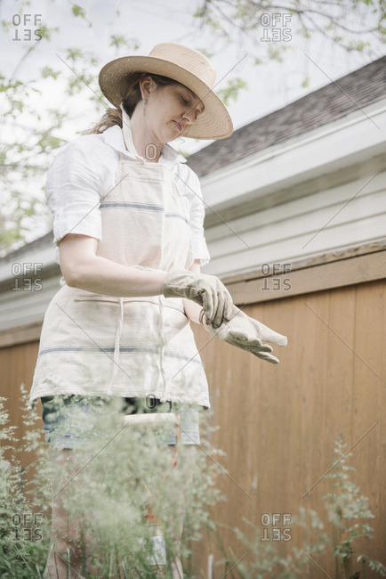 Woman wearing an apron, hat and gardening gloves, standing outdoors.