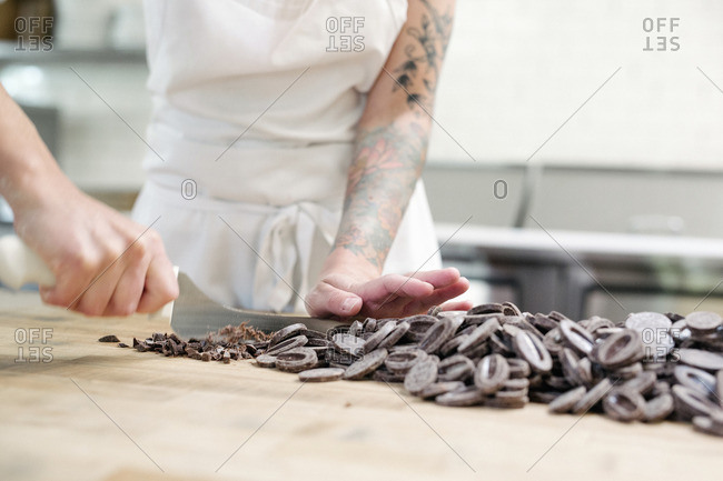 Close up of a woman wearing a white apron standing at a work counter in a bakery, chopping chocolate.