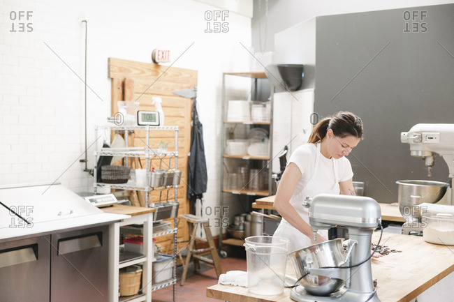Woman wearing a white apron standing at a work counter in a bakery.