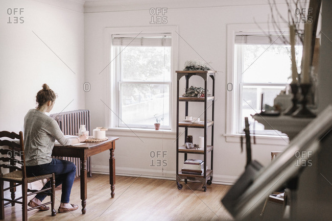 Woman sitting at a table in her apartment, writing in a diary, morning routine.