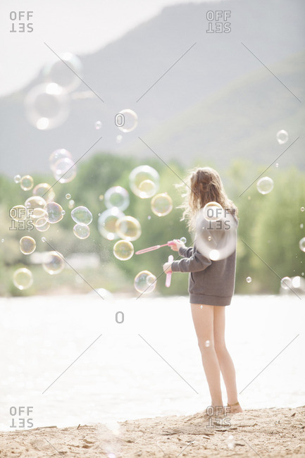 Teenage girl standing by a lake, surrounded by soap bubbles.