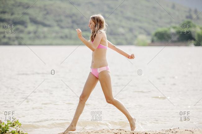 Teenage girls wearing a pink bikini running along a sandy beach by a lake.