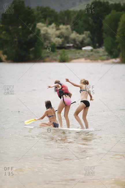 Three teenage girls on a paddle board on a lake.