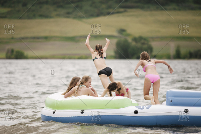 Teenage girls in an inflatable dinghy on a lake.