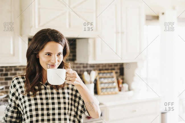 Woman with long brown hair, wearing a chequered shirt, drinking from a mug.