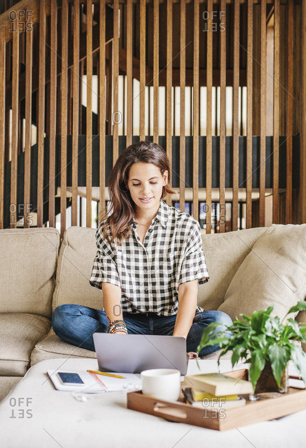 Woman with long brown hair sitting on a sofa with a laptop computer and notebook, working.