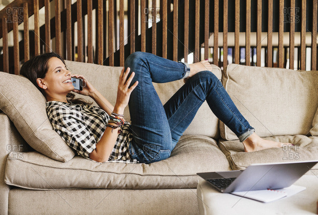 Woman with long brown hair lying on a sofa, using a mobile phone.