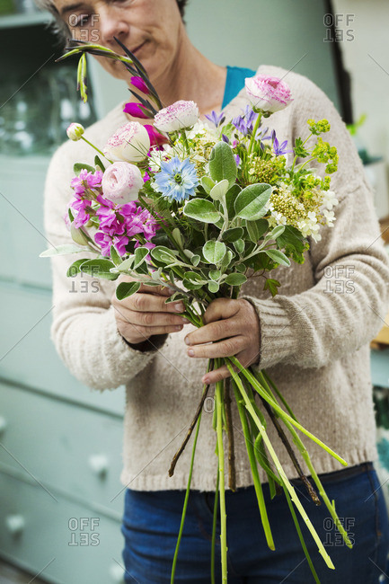 A florist creating a hand tied bunch of fresh flowers.