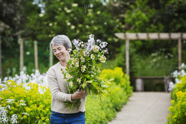A florist selecting flowers and plants from the garden to create an arrangement. Organic garden.