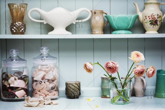 A shelf with vases and ceramic pots, and flowers in a vase.