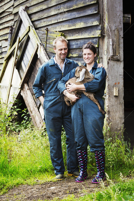 Man and woman standing outside a barn, holding a goat.