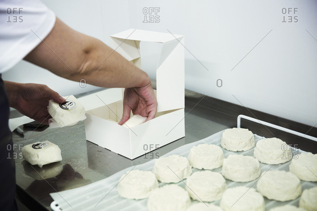 Close up of goats cheeses being packed into a box.