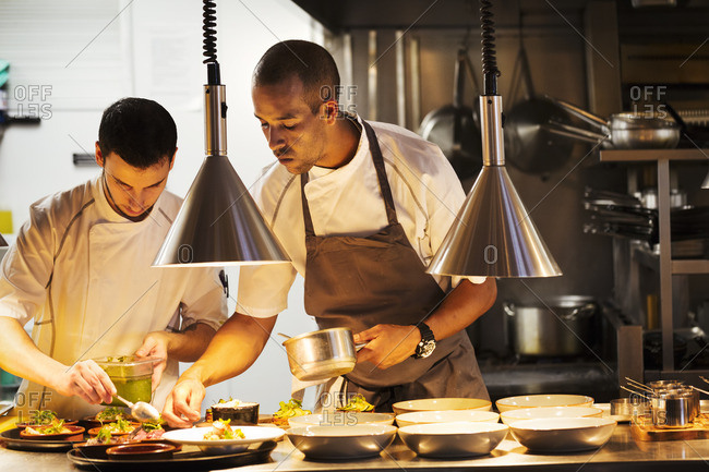 Two chefs standing in a restaurant kitchen, plating food.