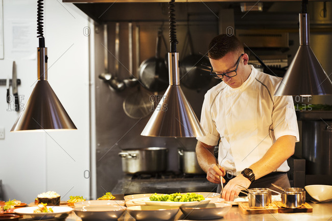 Chef standing in a restaurant kitchen, plating food.