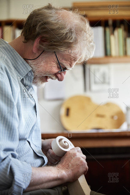 A violin maker using hand tools to smooth and finish a new wooden violin headstock, curled scroll of wood.