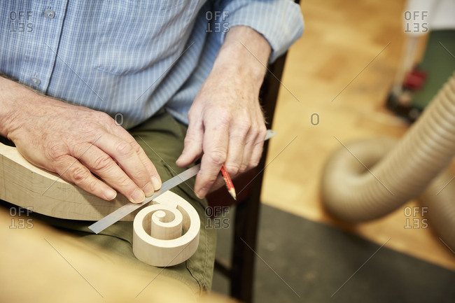 A violin maker using a ruler to measure the curled scroll of the violin headstock.