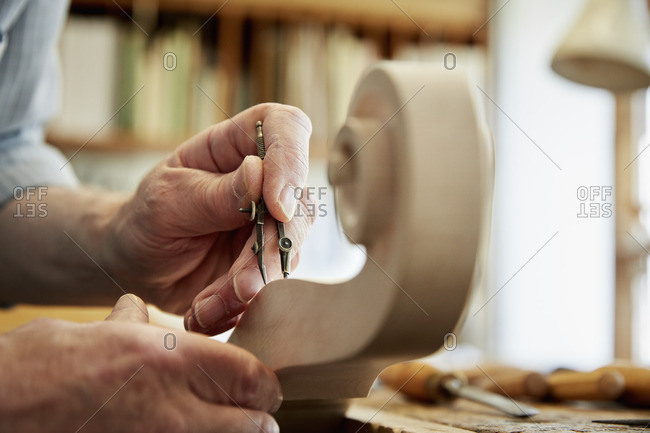 A violin maker working in his workshop, using hand tools to shape and chisel the curled scroll of the violin stock.