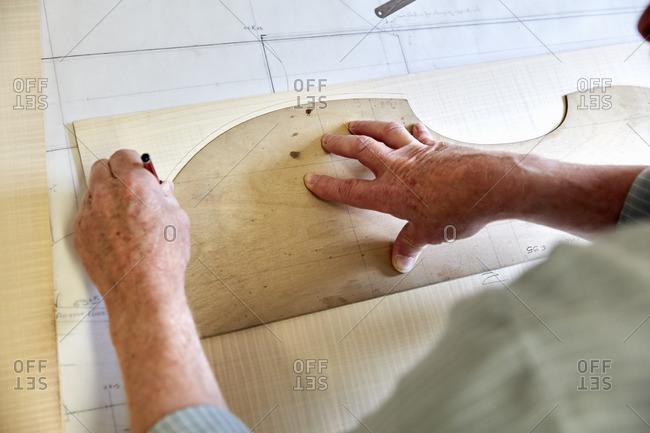 A violin maker's workshop. Skilled craftsman drawing around the outline of a wood back board for a violin.