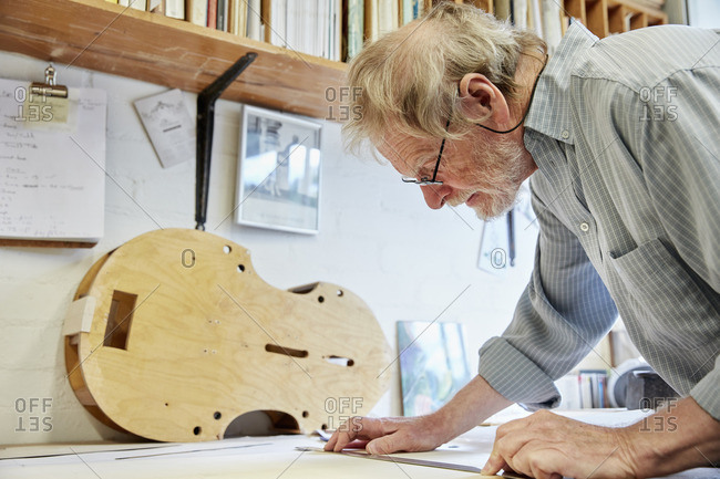 A violin maker at his drawing board drawing out the plans and outline for a new instrument.