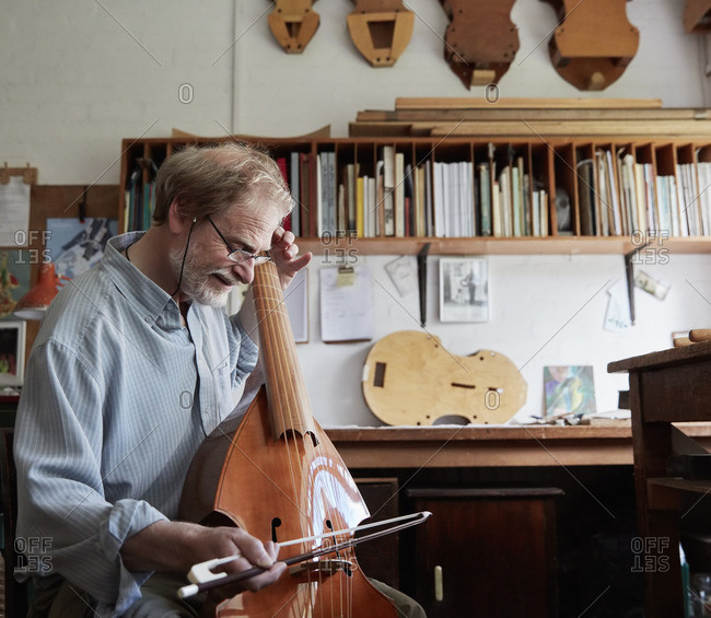 A violin maker in his workshop playing an instrument with a bow, tuning and finishing.