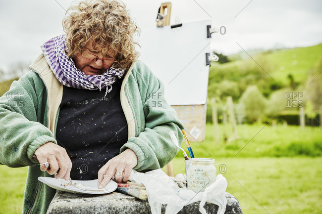 A woman artist working outdoors, sitting mixing or preparing paint on a paper plate.
