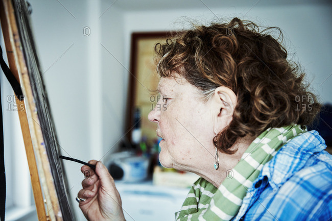 An artist working at her easel, using charcoal on paper to create an artwork.
