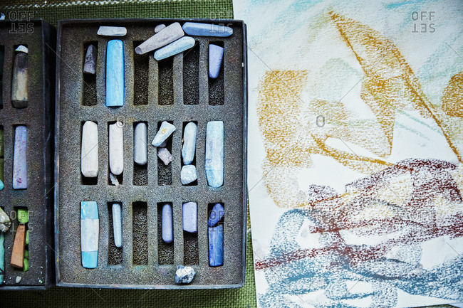 An artist's canvas with an artwork in progress, and box of pastels, colors.