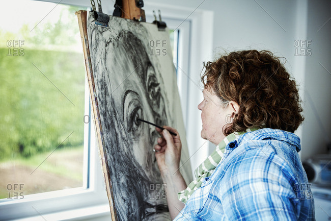 An artist working at her easel, using charcoal on paper drawing a portrait.