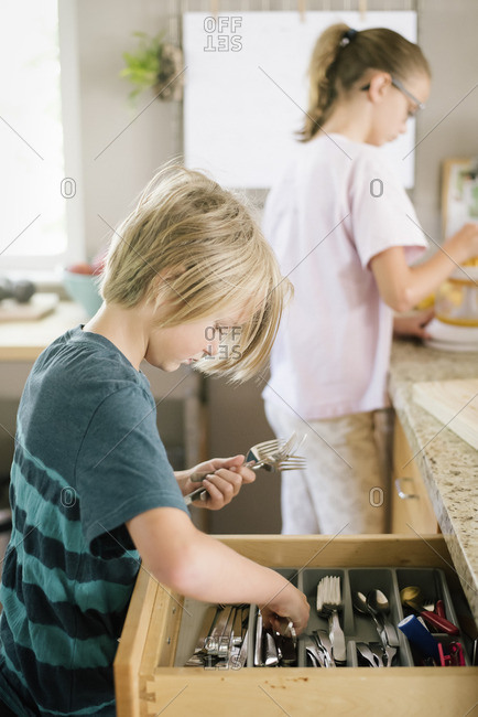 Family preparing breakfast in a kitchen, boy getting cutlery from a drawer.