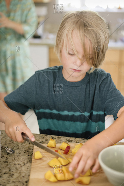 Family preparing breakfast in a kitchen, boy cutting fruit.