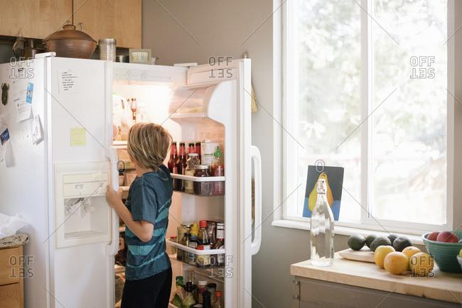 Family preparing breakfast in a kitchen, boy standing at an open fridge.