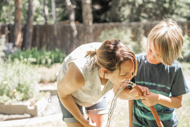 Mother and son standing in a garden, drinking water from a garden hose.