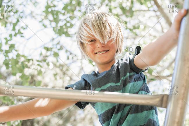 Blond boy on a climbing frame in a garden.