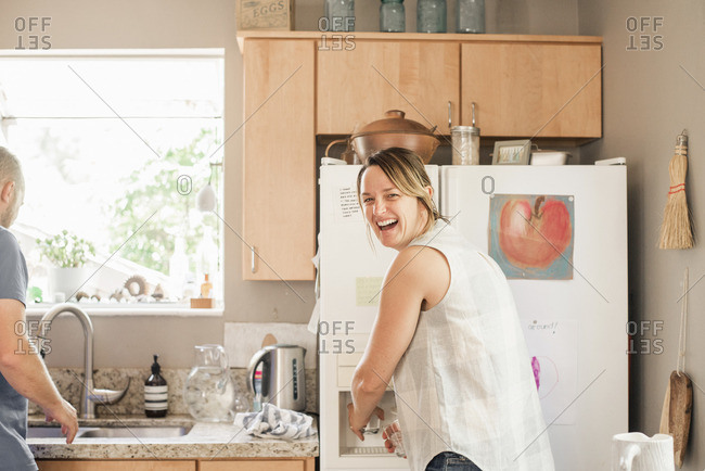 Smiling blond woman standing at a fridge in a kitchen.