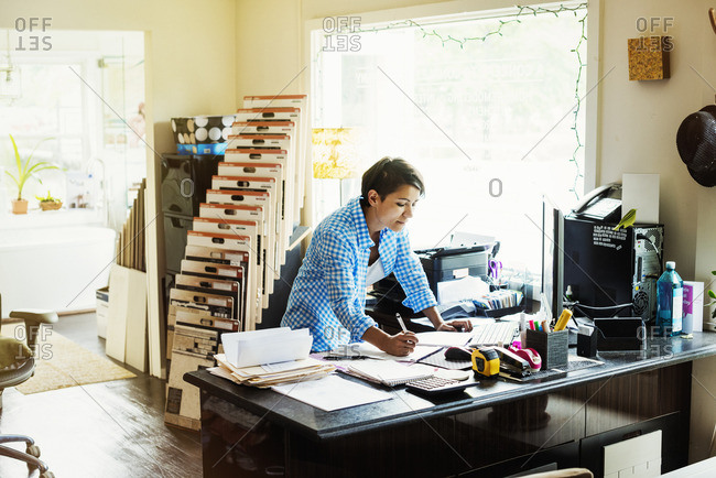 Woman working at a desk in an interior design studio and accessories store.
