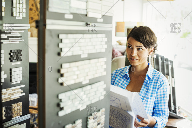 Woman looking at merchandise in an interior design store. Tile samples.