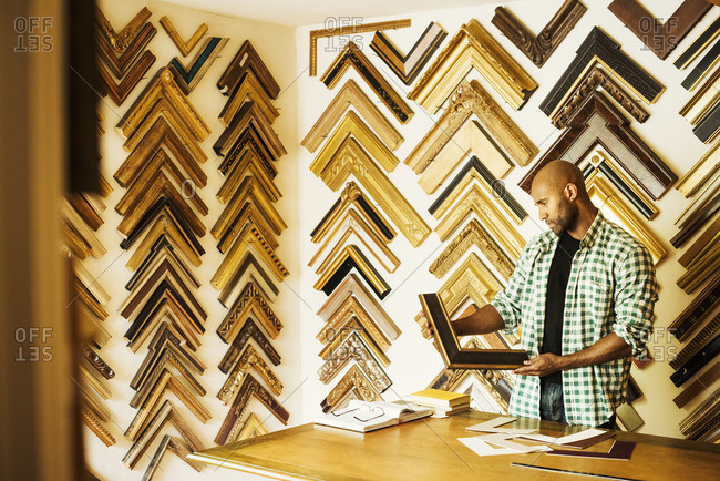 Man working at a picture framers, a large selection of frames on the walls.