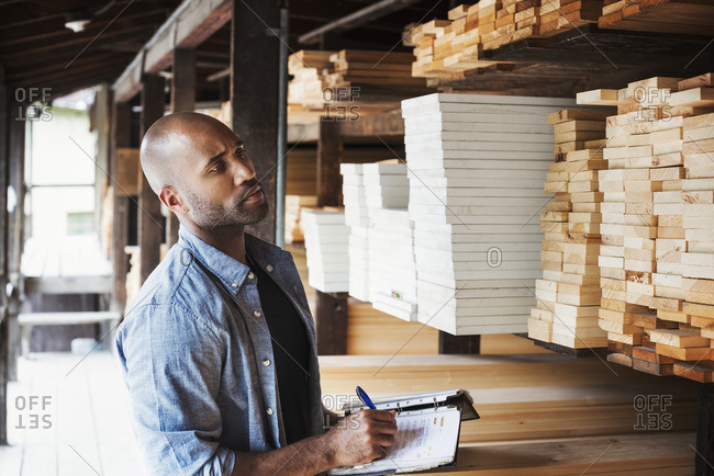 Man standing in a lumber yard, holding a folder, checking wood, writing notes.