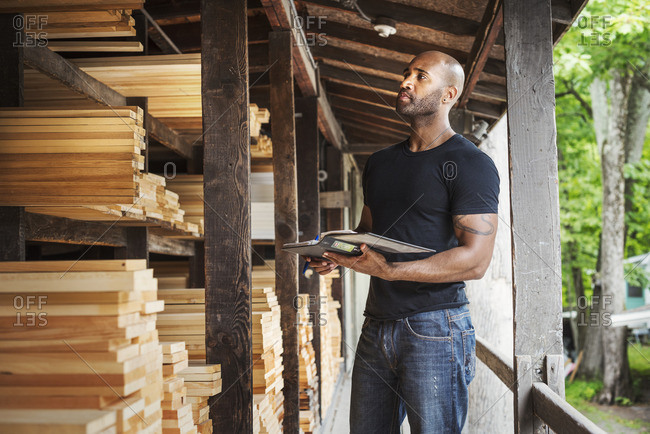 Man standing in a lumber yard, holding a folder, checking notes.