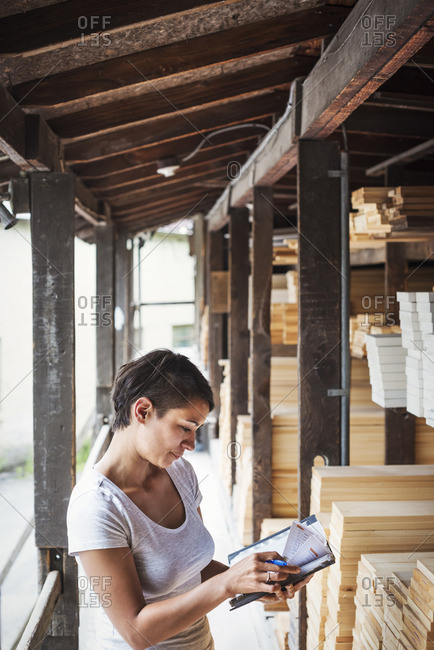 Woman standing in a lumber yard, holding a folder, checking notes.