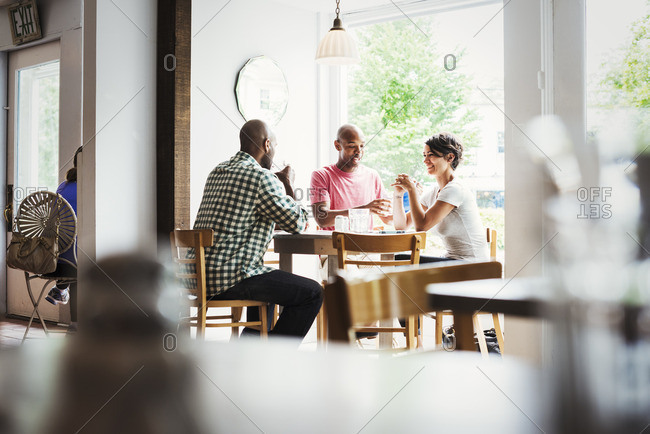 Two men and a woman sitting at a table in a cafe, having lunch.
