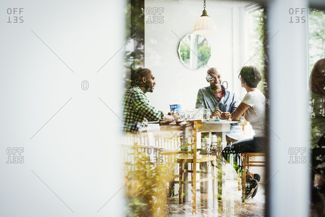 View through a window into a cafe, people sitting at tables.
