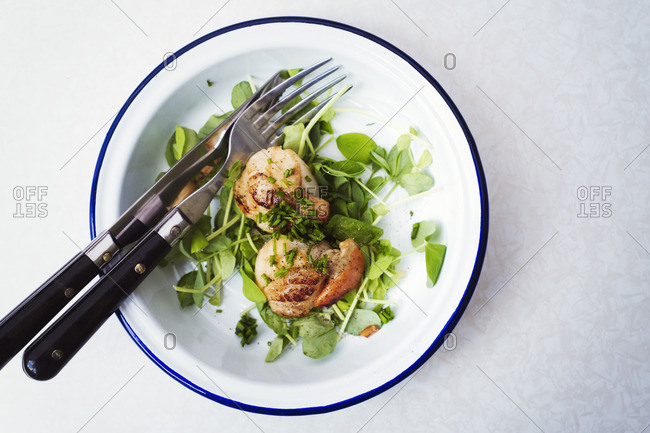 High angle view of two fried scallops on a plate, knife and fork.