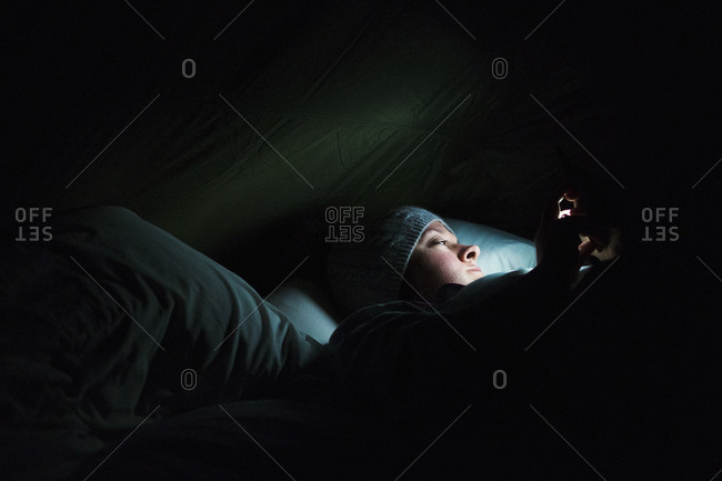 Woman lying in a tent at night, illuminated by a torch.