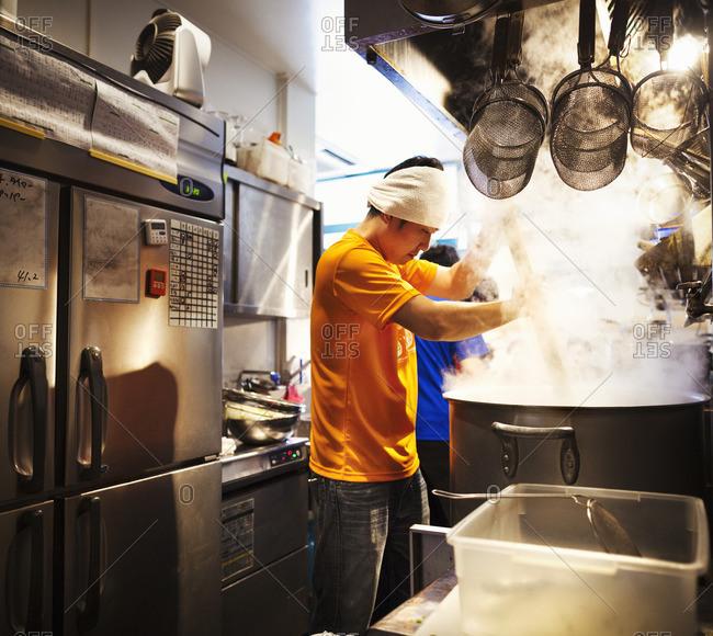 The ramen noodle shop, staff preparing food. Two men stirring a vat of noodles.